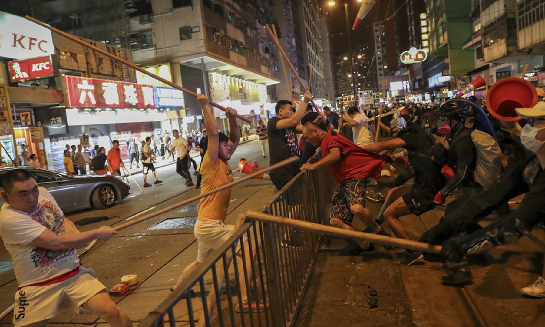 In this Aug 5, 2019, photo, protesters wearing black shirt (R) fight with a group of men wielding wooden poles on a street during the anti-extradition bill protest at a neighbourhood in Hong Kong. — AP