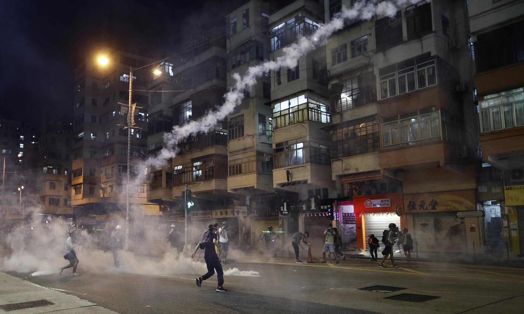 In this Aug 14, 2019, photo, protesters react to tear gas from Shum Shui Po police station in Hong Kong. — AP