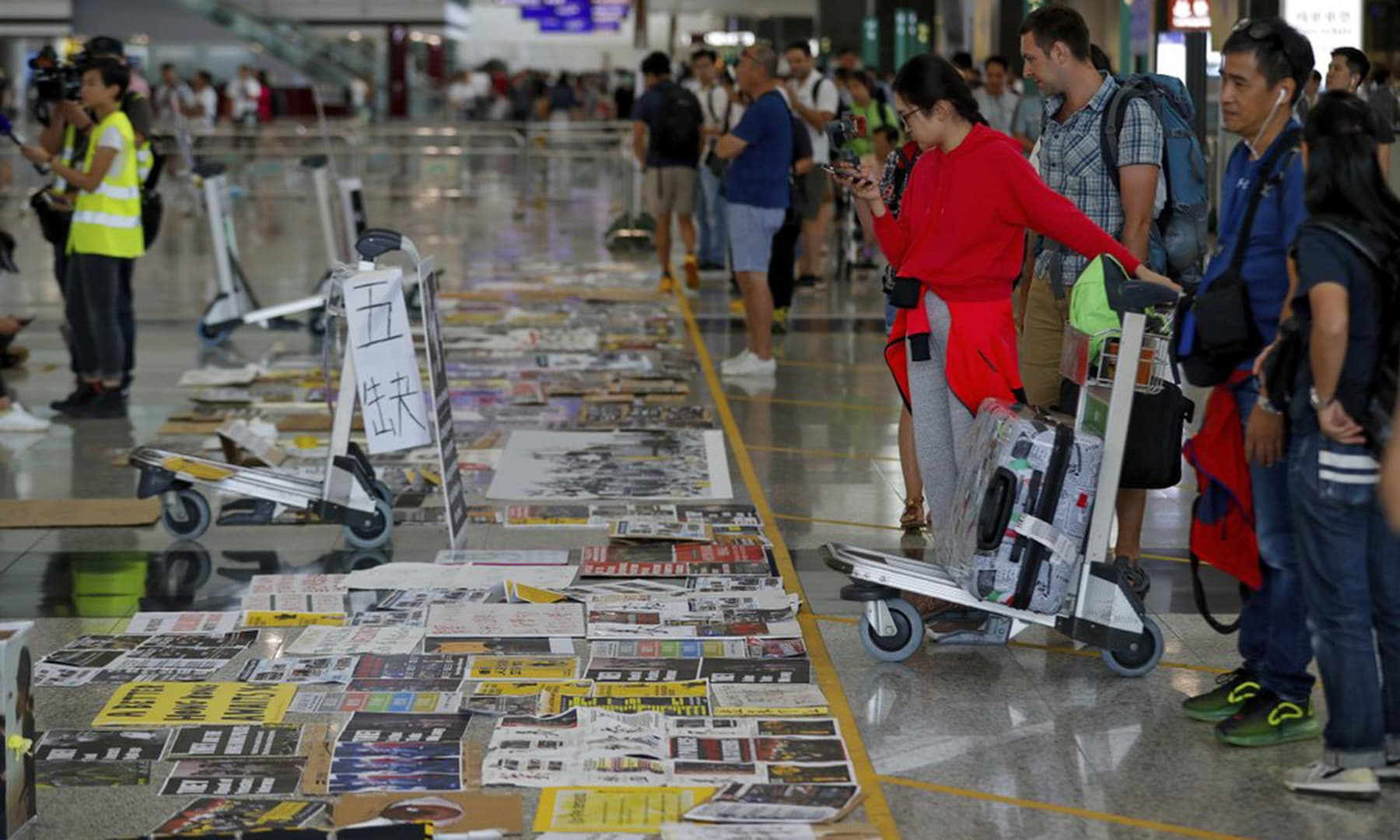 Travellers look at placards and posters placed by protesters at the airport in Hong Kong on Aug 14, 2019. — AP