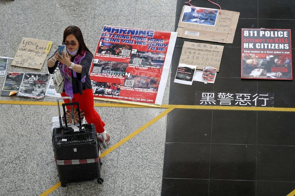 A traveller takes a photo near placards and posters placed by protesters at the airport in Hong Kong on Aug 14, 2019. — AP