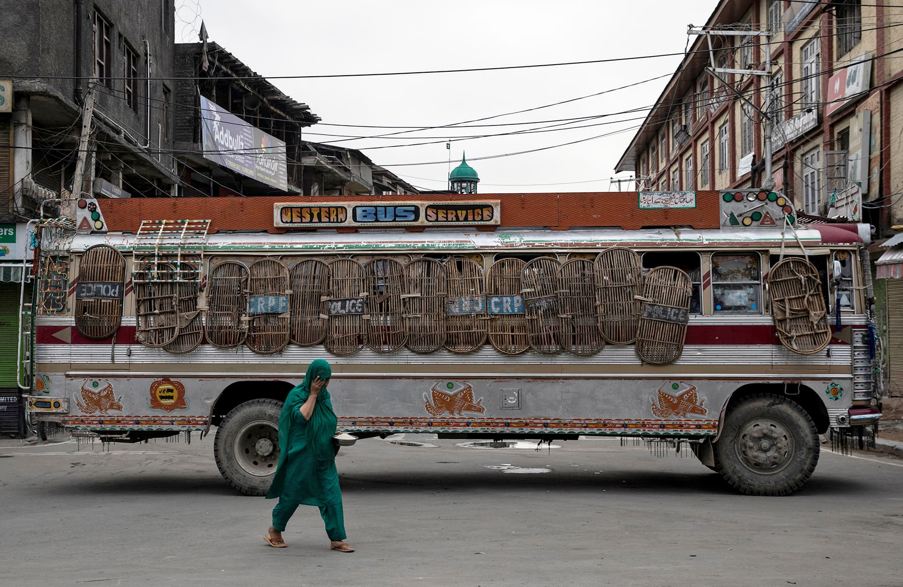 A Kashmiri woman walks past a bus used as a road block by Indian security personnel during restrictions, in Srinagar, August 11. — Reuters