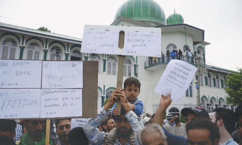 SRINAGAR: A young boy joins protesters holding aloft placards at a rally against India on Friday.—AFP