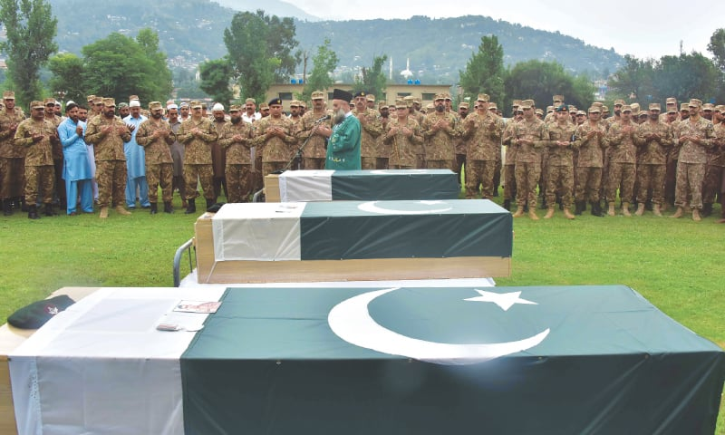 Muzaffarabad: Army officials and soldiers pray on Friday beside coffins carrying the bodies of three colleagues martyred in Indian shelling along the Line of Control on Thursday.—AFP