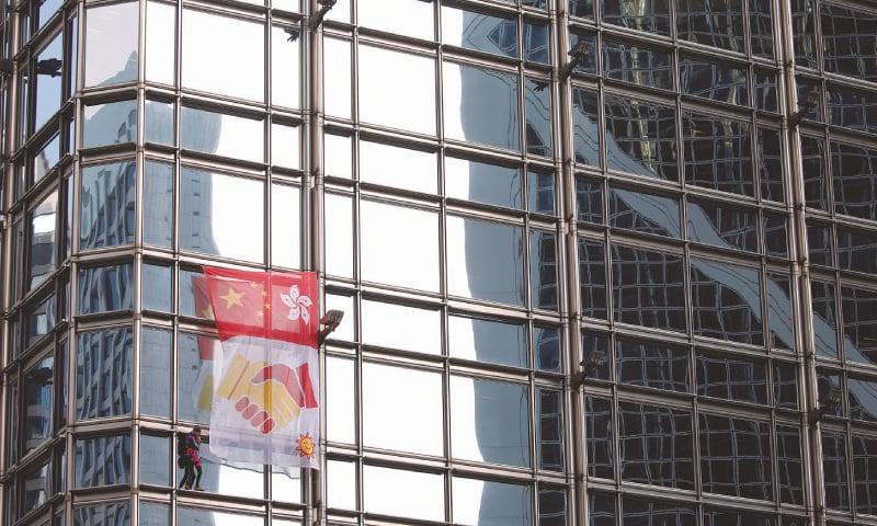 HONG KONG: French urban climber Alain Robert climbs the Cheung Kong Centre  on Friday.—Reuters