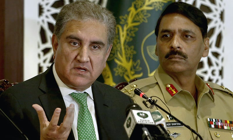 Foreign Minister Shah Mahmood Qureshi, left, speaks while military spokesman Maj Gen Asif Ghafoor looks on during a press conference in Islamabad on Saturday. — AP