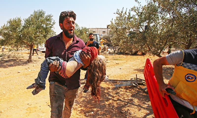 A Syrian carries the body of a child at the site of a reported regime air strike on the village of Deir Sharqi on the eastern outskirts of Maaret al-Numan in Syria's northern province of Idlib on August 17, 2019. — AFP