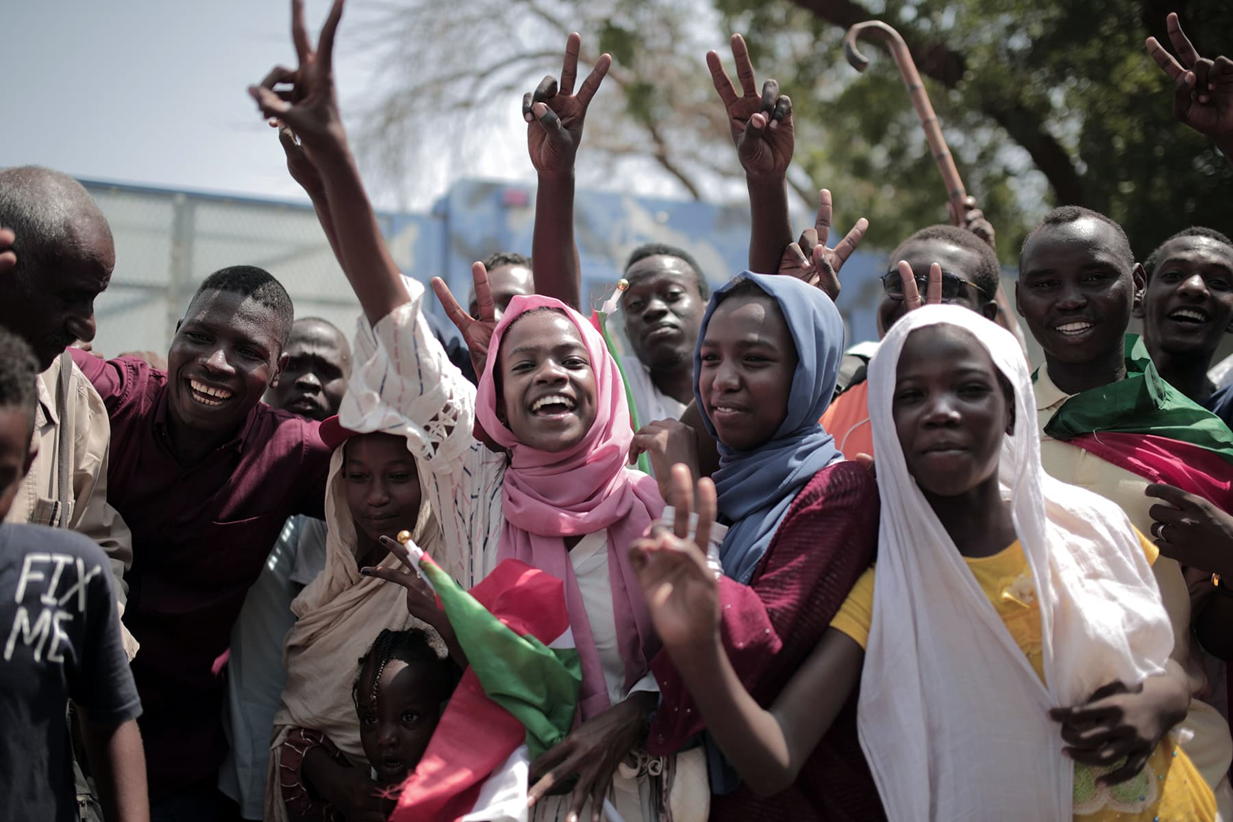 Sudanese men and women celebrate outside the Friendship Hall in the capital Khartoum where generals and protest leaders signed a historic transitional constitution meant to pave the way for civilian rule in Sudan, on Saturday. — AFP