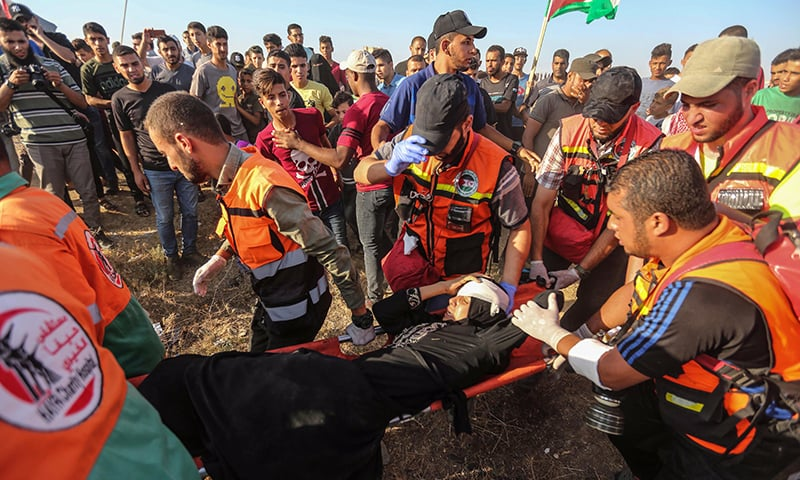 Palestinian paramedics carry a wounded protester during clashes with Israeli forces near the fence along the border with Israel in the eastern Gaza Strip on Friday. — AFP