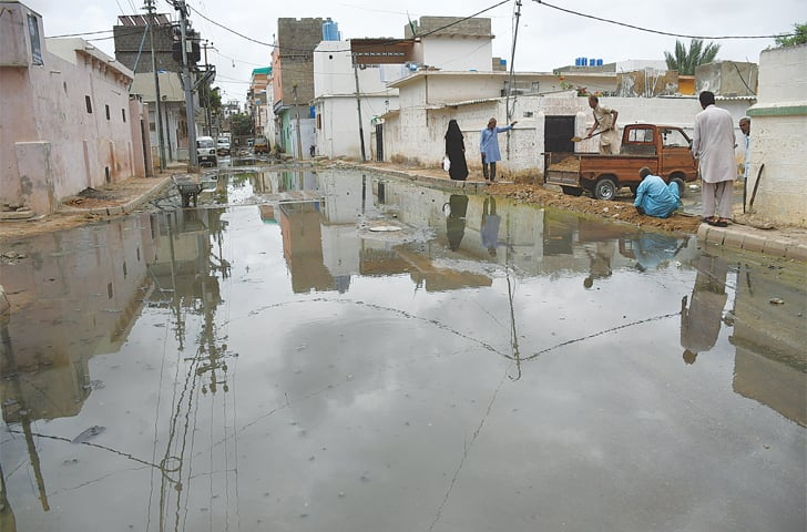 SEWAGE floods a neighbourhood in Martin Quarters on Saturday.—Faysal Mujeeb / White Star