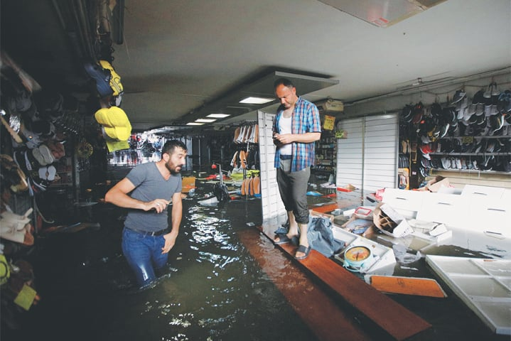 Shopkeepers try to save their goods at a flooded underground passage in Istanbul.—Reuters