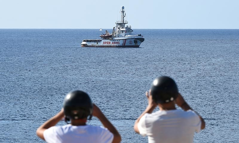 Tourists take pictures of the Spanish migrant rescue ship Open Arms close to the Italian shore in Lampedusa, Italy on August 17. — Reuters