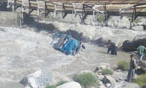 [ Volunteers try to pull the ill-fated jeep out of the river in Haramosh area of Gilgit.— Dawn/File