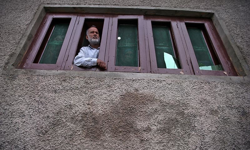A Kashmiri man looks out from a window of his house which was damaged allegedly by Indian security forces after clashes between protesters and the security forces on Friday evening in Srinagar in occupied Kashmir.  — Reuters