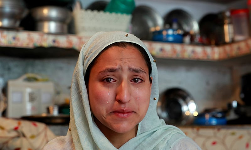 A woman weeps inside her house after her household goods were damaged allegedly by Indian security forces following clashes between protesters and the security forces on Friday evening. ─ Reuters