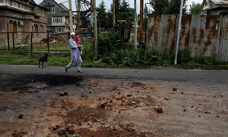 A Kashmiri man carries a child and walks on a road dotted with stones and bricks from earlier protests in Srinagar. ─ AP