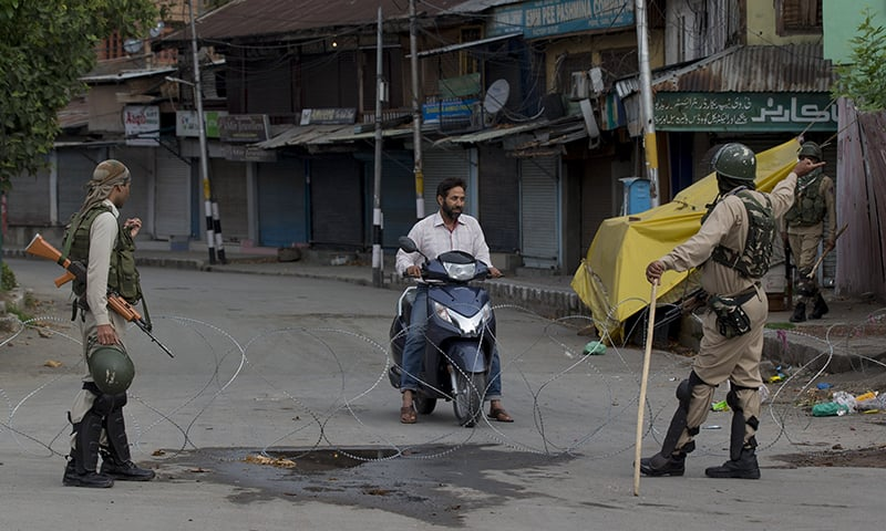 Indian paramilitary soldiers turn back a Kashmiri motorist near a temporary check point during lockdown in Srinagar on Sunday. — AP