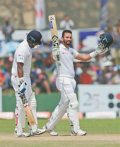GALLE: Sri Lankan captain Dimuth Karunaratne raises his bat and helmet to celebrate his century during the first Test against New Zealand on Sunday.—AP
