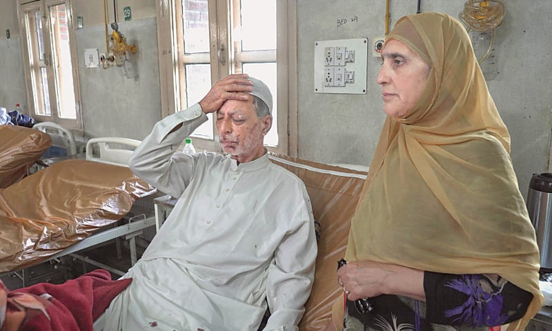 SRINAGAR: Mohammad Siddiq, 70, is under treatment at a hospital on Sunday as his wife stands beside him. The elderly man says he was returning home from a mosque when an Indian policeman fired a pellet gun at him, damaging his eye.—AP