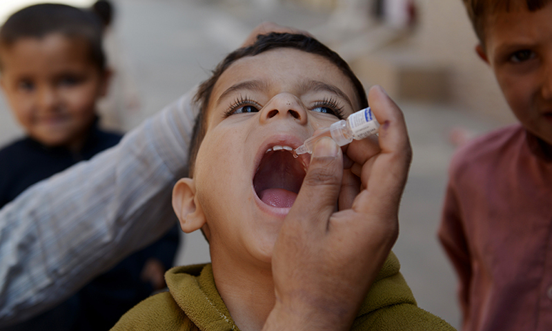 A child receives polio vaccination drops from a health worker.  — AFP/File