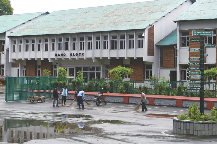 WORKERS clean the campus of a school in Srinagar on Monday.—AFP