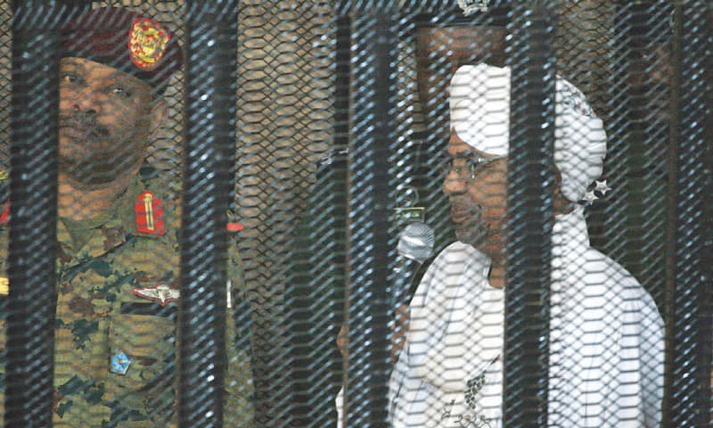 Khartoum: Sudan's deposed military ruler Omar al Bashir stands in a defendant's cage during the opening of his corruption trial on Monday. — AFP