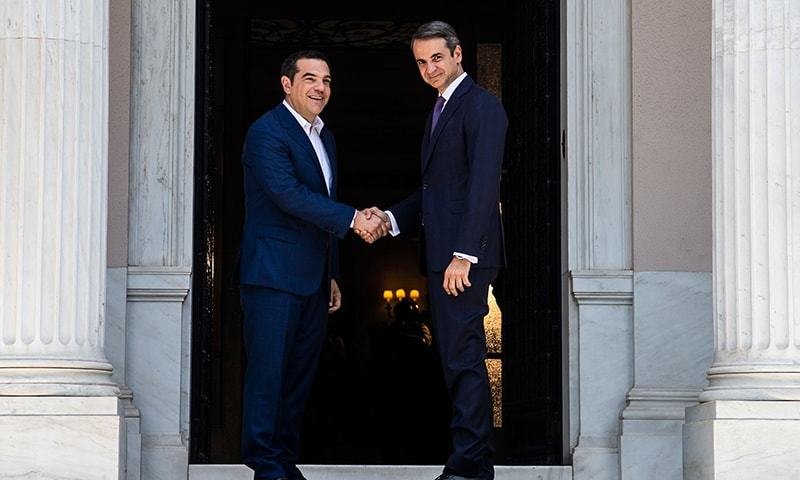 Newly-appointed Greek Prime Minister Kyriakos Mitsotakis (R) shakes hands with former prime minister Alexis Tsipras. — AFP/File