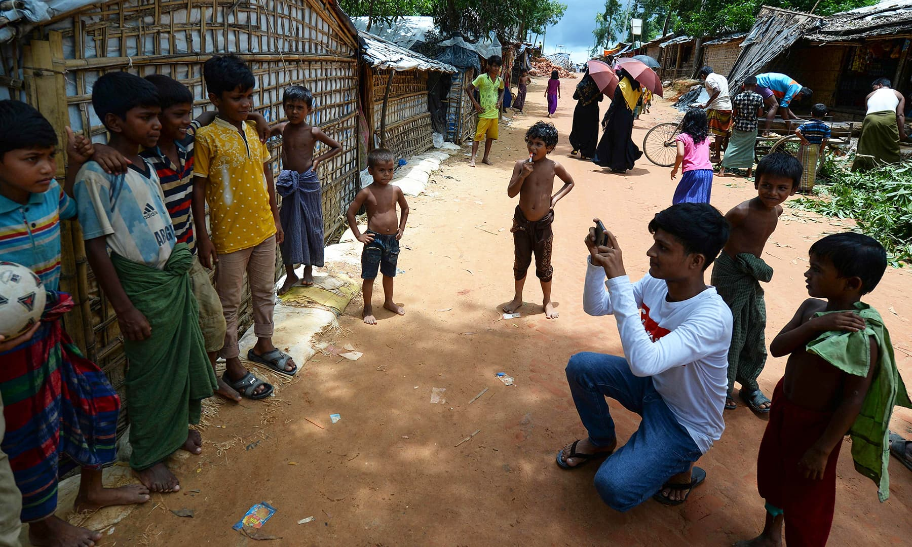 Rohingya youth Mohammad Rafiq (2nd R, in white) uses his mobile phone to take photos of children at the Kutupalong refugee camp. — AFP