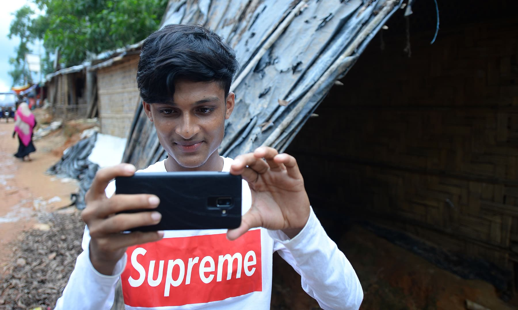 Rohingya youth Mohammad Rafiq uses his mobile phone to take photos at the Kutupalong refugee camp. — AFP