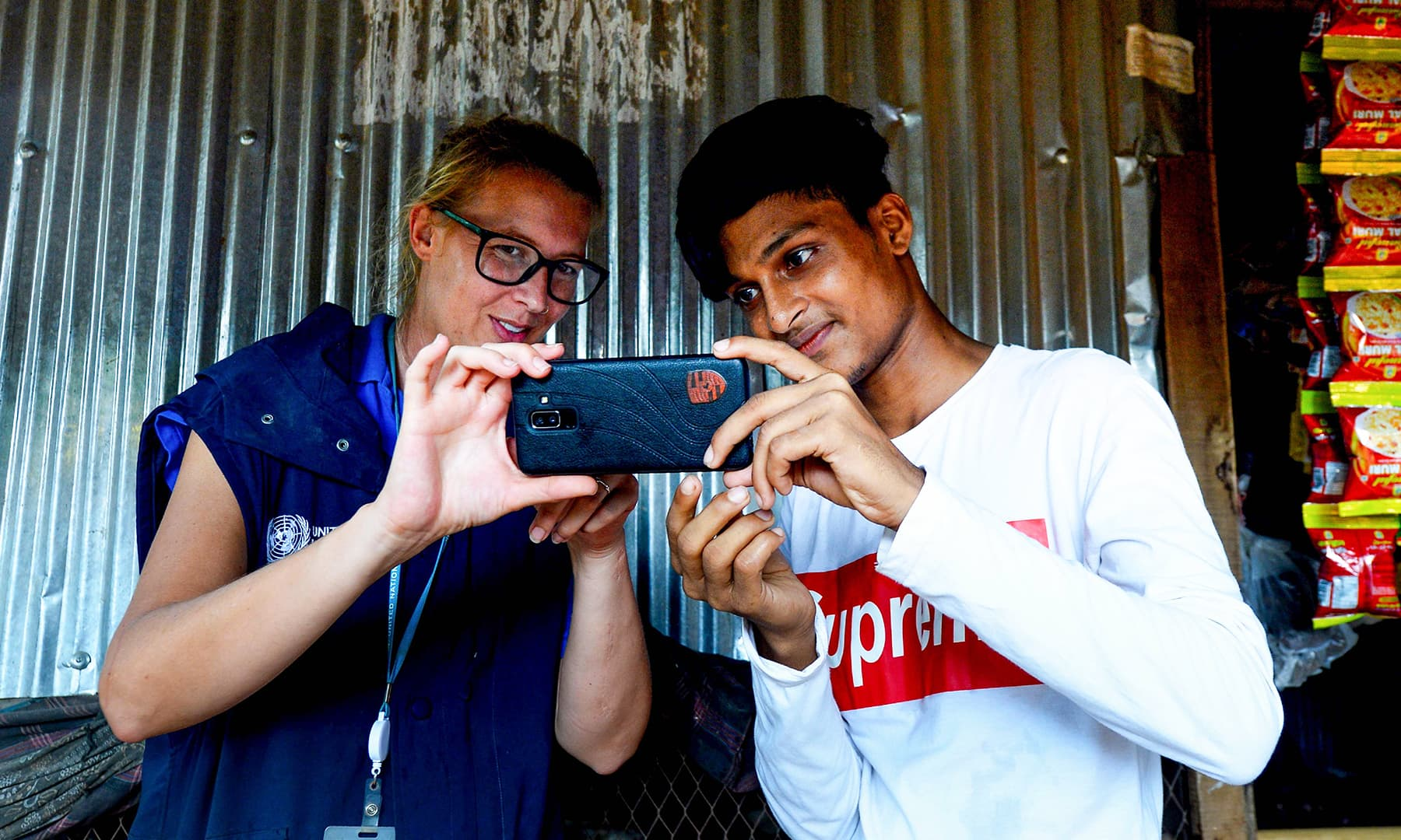 WFP official Gemma Snowdon coaches Rohingya youth Mohammad Rafiq on methods to take better photos with his mobile phone at the Kutupalong refugee camp. — AFP