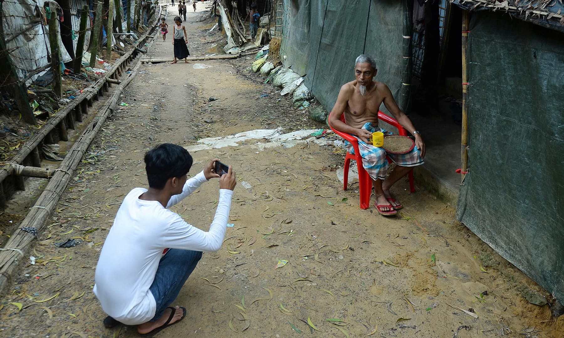 Rohingya youth Mohammad Rafiq uses his mobile phone to take photos of a man by his shack at the Kutupalong refugee camp. — AFP