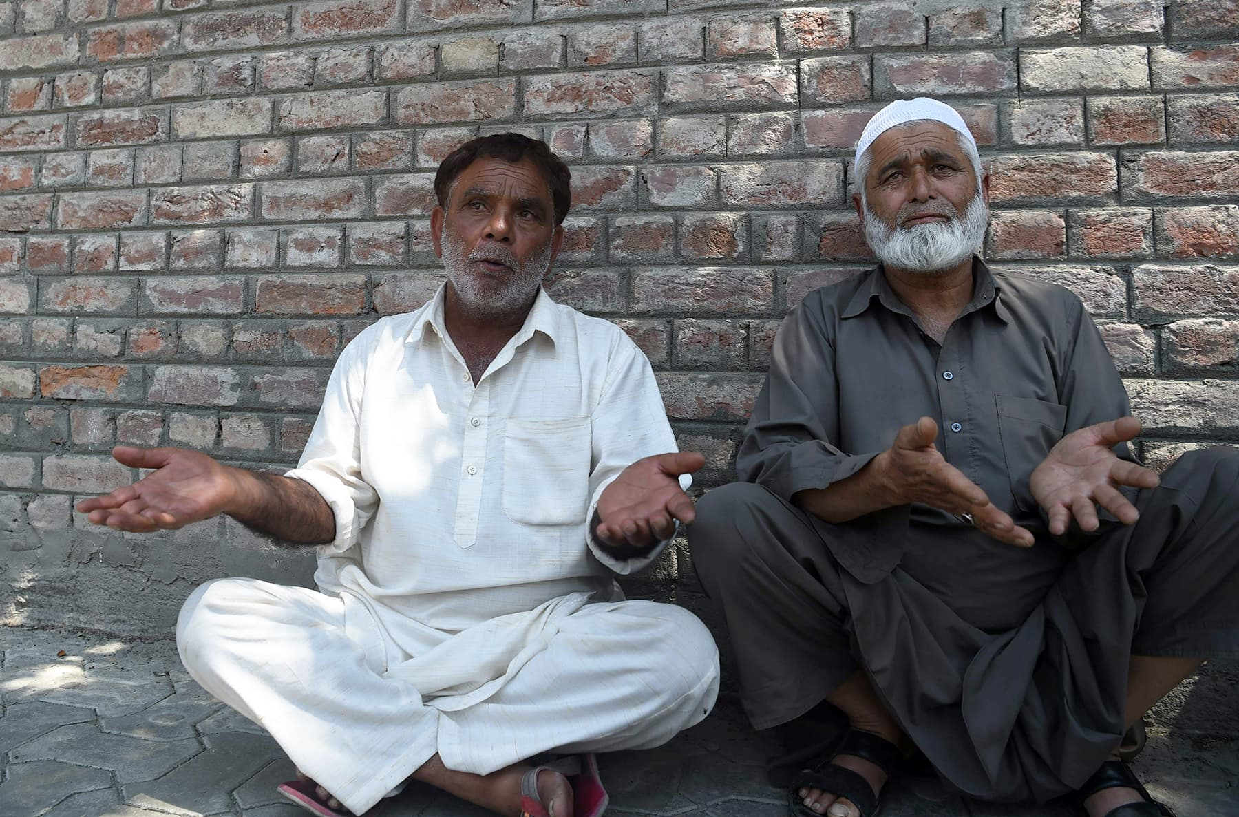 Two men speak to the media as they wait outside a police station after their sons were detained during night raids in Srinagar on Tuesday. — AFP