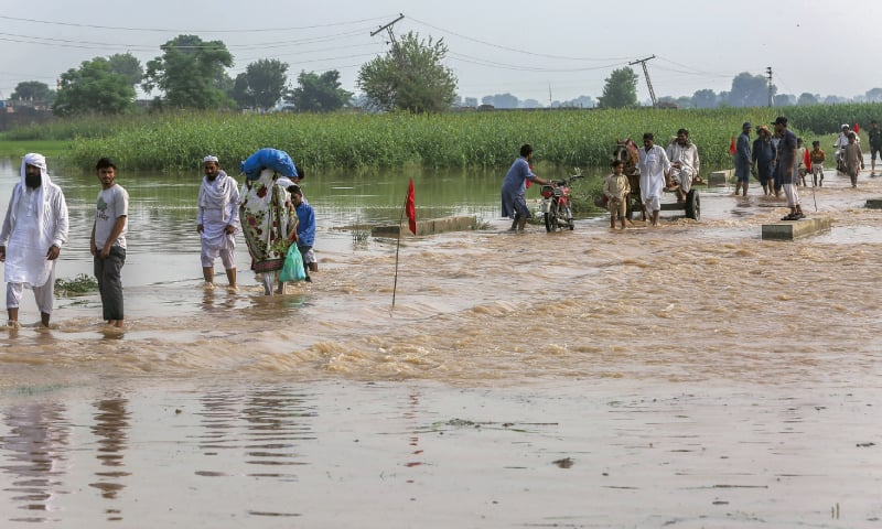 KASUR: People cross a flooded road on Tuesday.— Aun Jafri / White Star