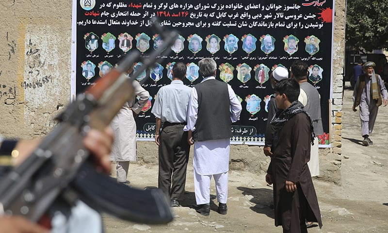 Afghans look at a banner displaying photographs of victims of the Dubai City wedding hall bombing during a memorial service, in Kabul, Afghanistan, on Tuesday. — AP
