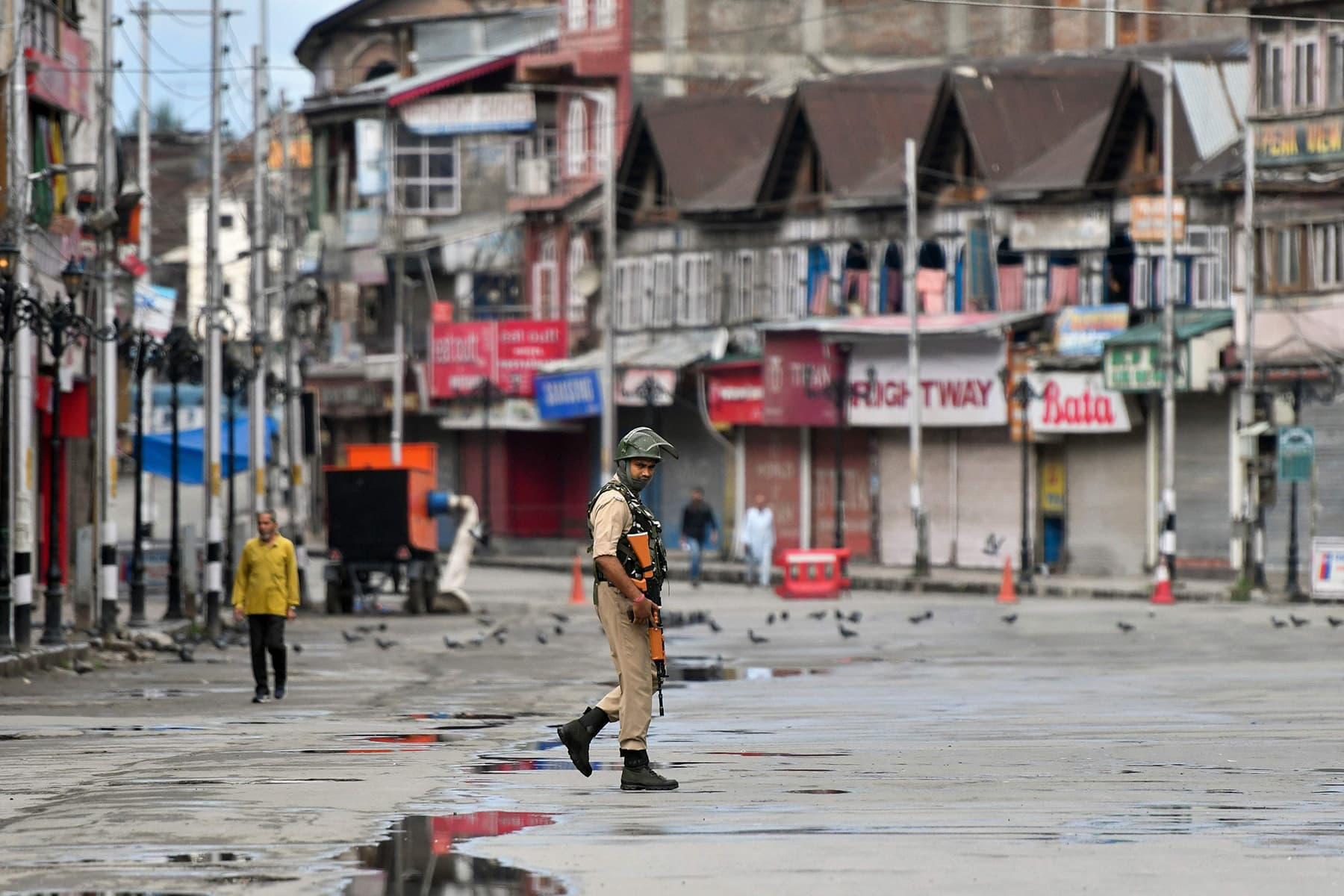 In this photo taken on August 19, a security personnel patrols on a deserted road of the Lal Chowk area in Srinagar. — AFP