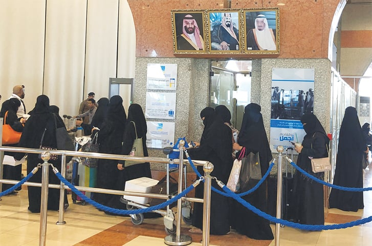 DAMMAM (Saudi Arabia): Women are seen in line at a railway station here on Wednesday. The kingdom has begun implementing a landmark reform allowing women over the age of 21 to receive passports and travel without permission from a male 'guardian'.—Reuters