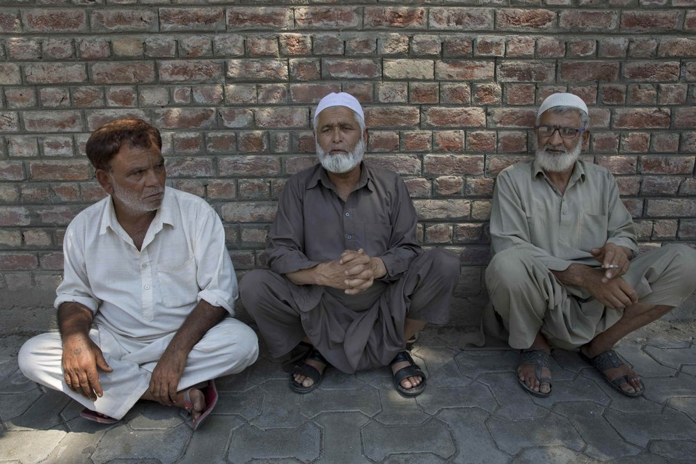 Kashmiri men sit on a footpath outside a police station waiting to hear about their relatives who were detained during night raids in Srinagar, on August 20. ─ AP