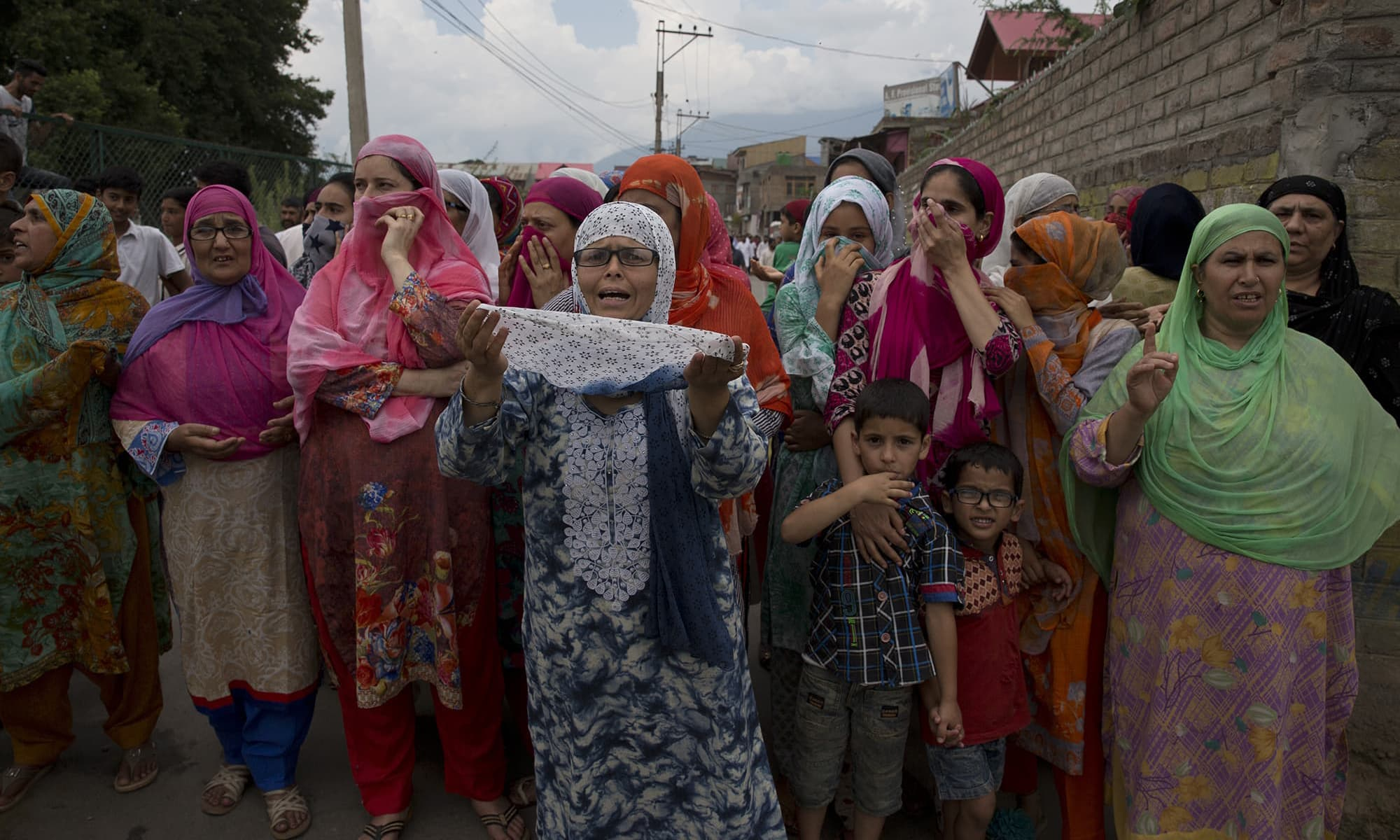 In this August 9 photo, a Kashmiri woman prays as she watches a protest march in Srinagar. — AP