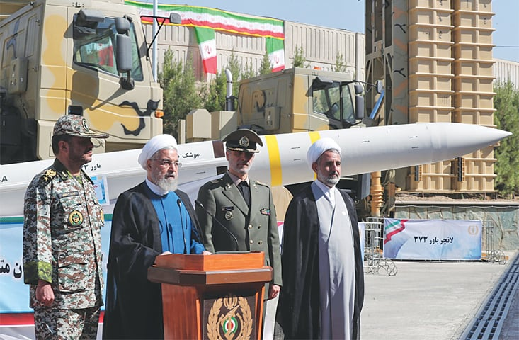TEHRAN: President Hassan Rouhani (second left) at the unveiling ceremony of the new Iranian-made missile defence system on Thursday.—AFP