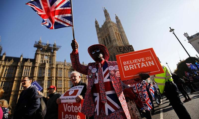 (FILES) In this file photo taken on February 27, 2019, pro-Brexit activists march outside the Houses of Parliament in central London. - With Britain deadlocked on negotiating its divorce from the European Union, an unexpected side-front is emerging -- the US Congress. Conservatives who pushed the June 2016 referendum that ended in the shock decision to leave the 28-member bloc dangled the prospect of a free trade agreement with the United States as proof that Britain would not be isolated. (Photo by Tolga AKMEN / A