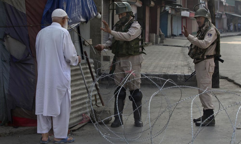 An elderly Kashmiri man is stopped before being allowed to pass near a temporary checkpoint set up by Indian paramilitary soldiers during lockdown in Srinagar on Friday. — AP