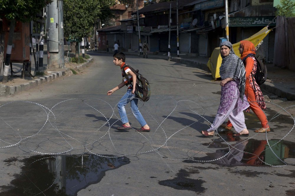 Kashmiri children accompanied by their mother walk past barbwire setup as road blockade by Indian paramilitary soldiers during lockdown in Srinagar, on Friday. ─ AP