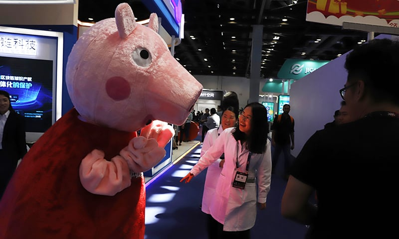 In this April 27, 2018 file photo, a woman reacts to a Peppa Pig mascot during the Global Mobile Internet Conference in Beijing, China. — AP