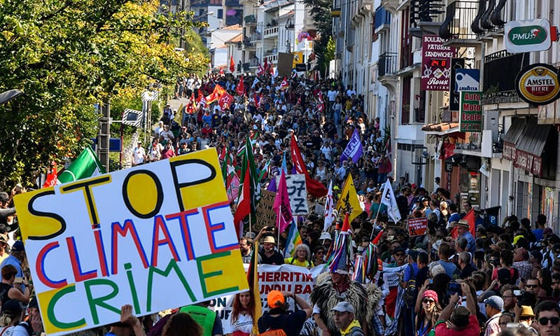 A placard reading 'stop climate crime' is seen as demonstrators take part in a march in Hendaye, south-west France on Saturday to protest against the annual G7 Summit attended by the leaders of the world's seven richest democracies, Britain, Canada, France, Germany, Italy, Japan and the United States. — AFP