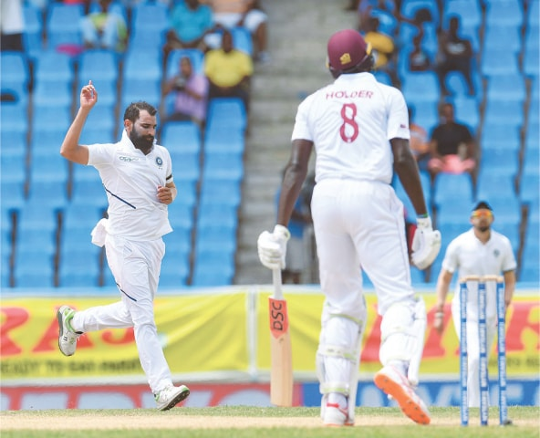 INDIAN paceman Mohammed Shami celebrates after dismissing West Indies' skipper Jason Holder during the first Test at the Sir Vivian Richards Stadium on Saturday.—AFP