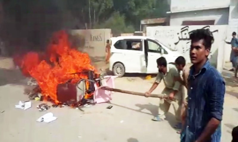 Violent protesters in Karachi's Ahsanabad cooperative housing society are seen torching objects on Sunday as authorities attempted to remove encroachments from the area. — DawnNewsTV