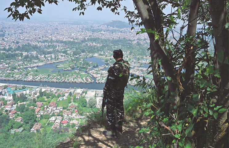 AN Indian paramilitary soldier patrols atop a hill overlooking occupied Srinagar on Sunday.—AFP