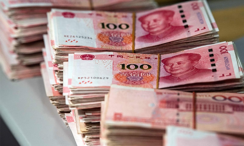 This file photo taken on August 8, 2018 shows bundles of 100 yuan notes at a bank in Shanghai. - China's currency on August 26, 2019 slid to its lowest point in more than 11 years as concerns over the US trade war and the potential for global recession weighed on markets. Photo: AFP