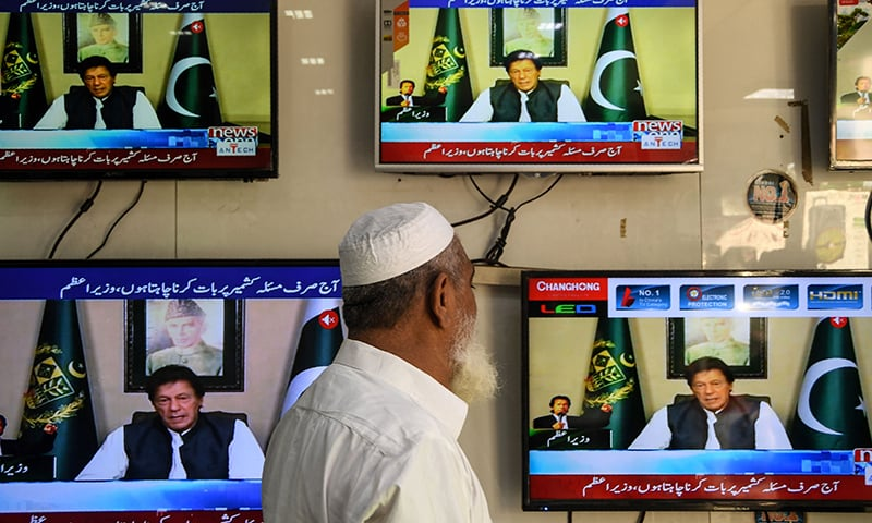 A man watches TV as Prime Minister Imran Khan speaks to the nation on Kashmir, at an electronic market in Karachi. — AFP
