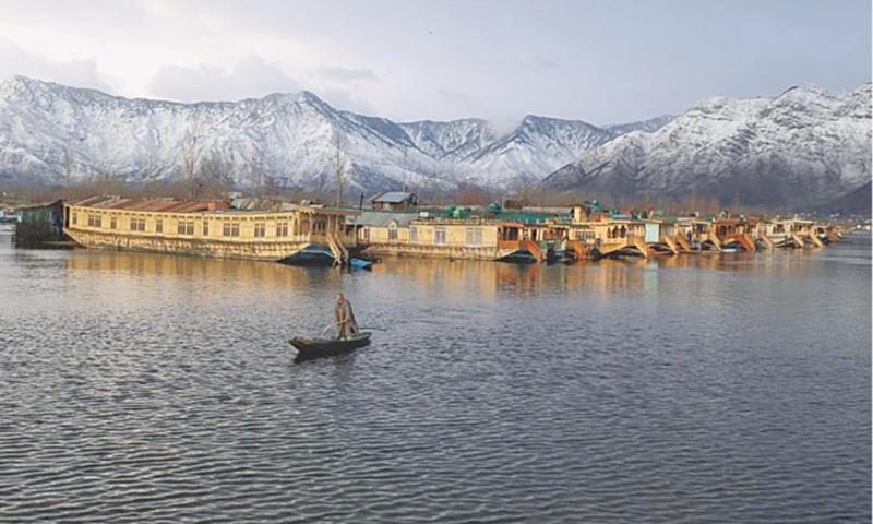 سری نگر کی ایک سرد شام میں ایک کشمیری ڈال جھیل پر کشتی چلا رہا ہے—دانش اسماعیل/رائٹرز