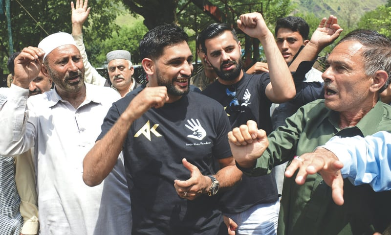 MUZAFFARABAD: Boxer Amir Khan meets Kashmiris living along the Line of Control in Chakoti area on Tuesday. — AP